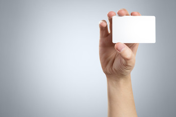 Hand holding a blank card or a ticket/flyer on gray background