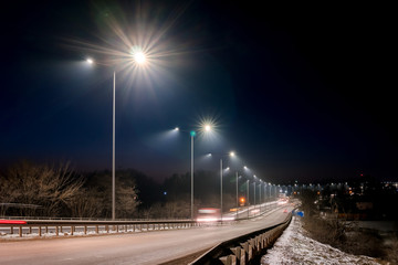 Fast moving traffic at night. winter season. concept of the road, snow and ice removal, danger and safety of movement, street lighting with energy-saving lamps Fotomurales