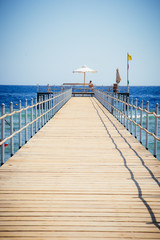 A wooden pier with sun loungers and umbrellas against the turquoise sea and azure sky.