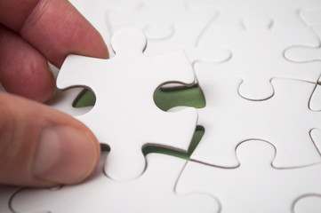 Man putting with hand the last piece of jigsaw puzzle on green background to complete the mission