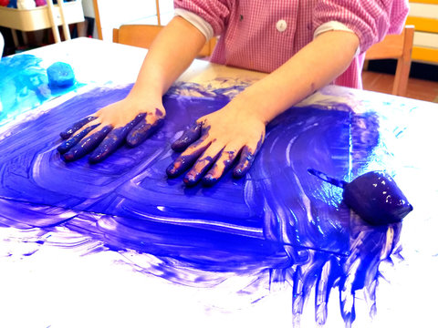 closeup of children hands painting during a school activity - ice painting -  learning by doing, education and art, art therapy concept