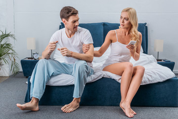 young woman holding smartphone and touching angry boyfriend sitting on bed, distrust concept