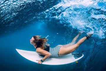 Surfer girl with surfboard dive underwater with fun under ocean wave.