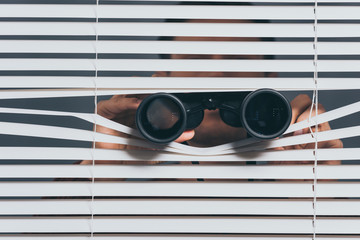 suspicious young man with binoculars spying through blinds - fototapety na wymiar