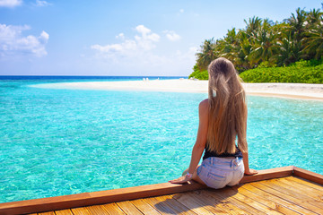 Holiday vacation beach - beautiful young girl relaxing and watching on wood lounger on paradise caribbean maldive beach with white sand and palms near blue sea on warm summer day