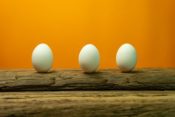 Three Eggs on a old oak wooden table orange background.