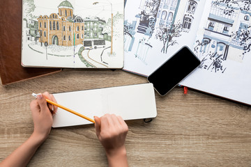 top view of womans hands holding pencil, albums with paints and smartphone on wooden background