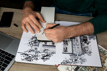 top view of mans hands drawing in notebook on wooden table next to albums and gadgets