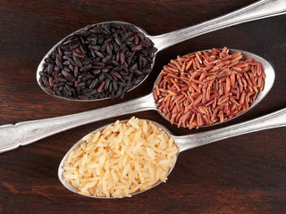 Uncooked black, red and integral rice in olive wood bowls, on a rustic wooden board, flat lay
