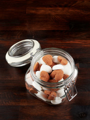 A jar filled sith white and brown heart shaped sugar cubes, on a dark wooden board