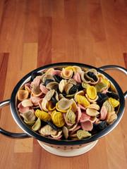 Colorful uncooked orecchiette pasta in a small colander