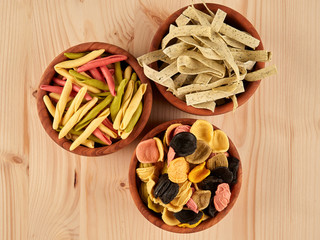 Three olive wood bowls with uncooked, colorful orechiette, fusilli and tagliatelle pasta, flat lay