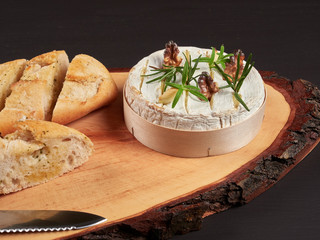 Baked Camembert with walnuts, rosemary stalks and garlic cloves, served with crusty garlic gread, on a rustic board