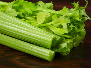 Fresh green celery stalks on a dark rustic wooden oak board