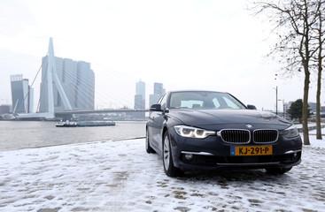 A BMW hybrid car stands near Rotterdam's Erasmus bridge