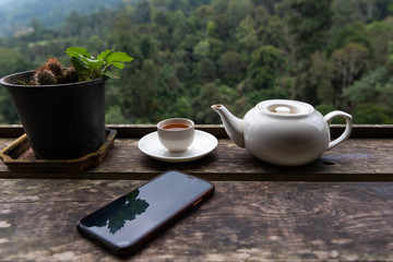 Tea with Tea pot and smart phone on wooden table in tea plantation