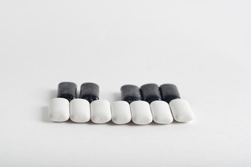 black and white chewing gum on white background. piano shaped