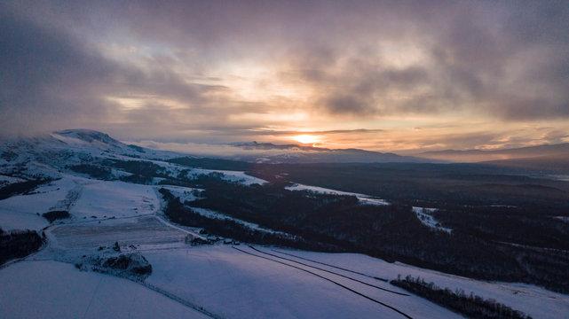 Foggy winter sunrise in the snowy mountain.
