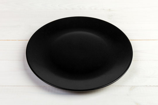 Perspective view. Empty black matte plate on white wooden background