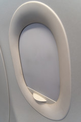 The window of the airplane. A view of porthole window on board an airbus for your travel concept or passenger air transportation.