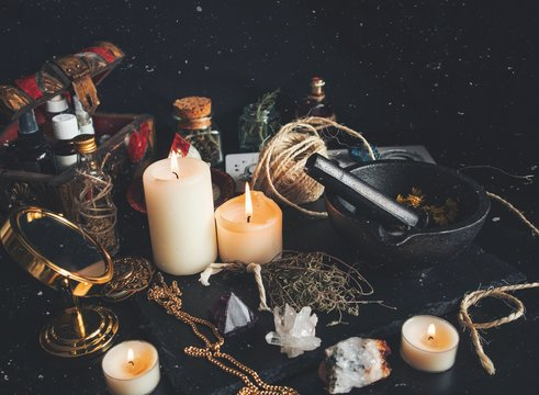 Witch's working space. A very messy witch's altar filled with random tidbits like mortar and pestle, burning white candles, gold mirror, dried herbs flowers, crystals and a chest box with oils