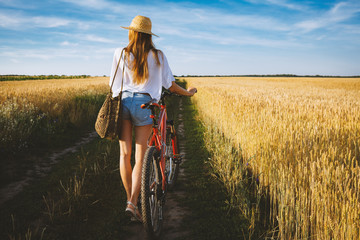 Girl in wheat summer field with bicycle