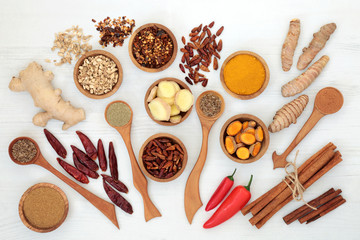 Herbs and spices for weight loss with turmeric, cumin, ginger, chilli, cinnamon and gymnema sylvestre used to suppress appetite. Top view on rustic wood background.