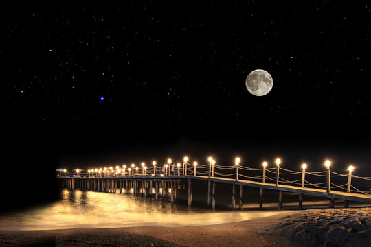 Fantastic summer night with full moon and illuminated pier on beach.