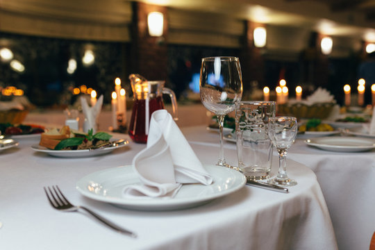 dinner set arranged on a table with vintage cream lace tablecloth and napkins, elegant porcelain dishes, silverware and crystal glassware