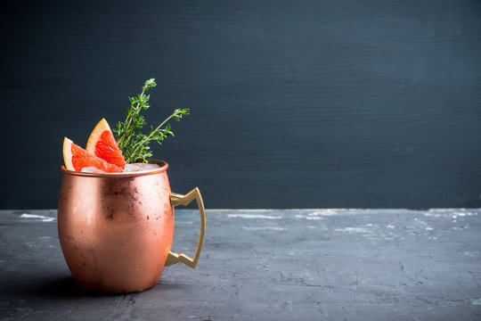 Grapefruit moscow mule in copper mug on the rustic background. Selective focus. Shallow depth of field.