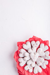 White heart shaped Valentine's day cookies with white glaze and coconut flakes on a red napkin. Copy space. Flat lay