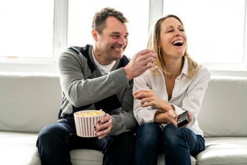 A Happy young couple lying on the sofa at home with popcorn watching TV