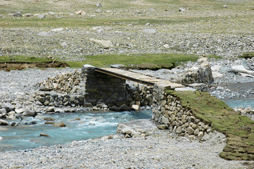 Bridge over the river on the way sacred bypass mount Kailash on the background of gray clouds, Tibet, China
