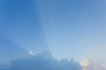 Beautiful morning blue sky background with soft long sunrays shining behind white fluffy cloud outside. Horizontal color photography.