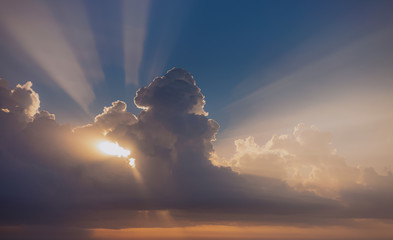 Beautiful dramatic early morning sky with soft charming white straight real sunrays from over fluffy white clouds isolated on blue and golden heaven background. Color horizontal photography.
