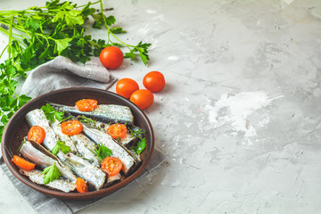 Sardines with tomatoes slices and spaces on ceramic plate