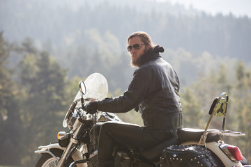 Back view of bearded motorcyclist with long hair in black leather jacket sitting on cruiser motorcycle on blurred background of spruce tall trees and hills on horizon. Active lifestyle and traveling.