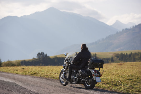 Back view of biker in black leather jacket riding cruiser motorcycle along road on blurred copy space background of beautiful foggy mountain range and cloudy sky on bright sunny day.