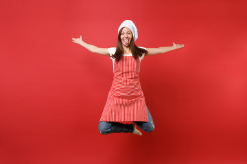 Housewife female chef cook or baker in striped apron white t-shirt, toque chefs hat isolated on red wall background. Full length portrait housekeeper woman jumping high up. Mock up copy space concept. - fototapety na wymiar