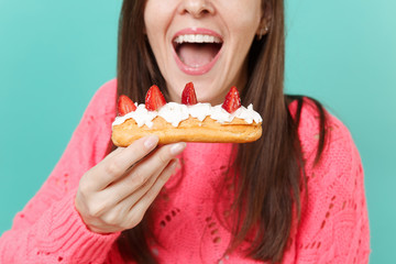 Cropped image of young woman in knitted pink sweater hold in hand eating, biting eclair cake isolated on blue turquoise wall background, studio portrait. People lifestyle concept. Mock up copy space.