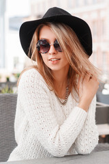 Beautiful attractive young woman in a white vintage knitted sweater in an elegant hat in fashionable sunglasses is resting on a warm spring day in a street cafe. Charming joyful blonde girl.