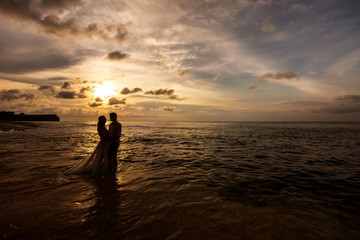 Silhouettes of bride and groom embracing standing in the sea water on the beach at sunset