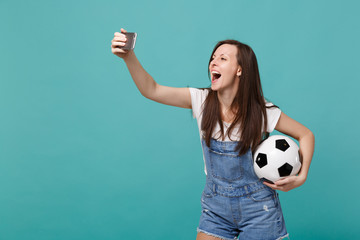 Cheerful young woman football fan with soccer ball doing selfie shot on mobile phone isolated on blue turquoise background. People emotions, sport family leisure lifestyle concept. Mock up copy space.