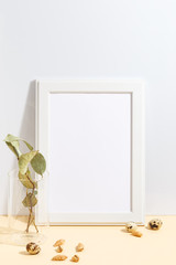 Mock up white frame and branch with green leaves in blue vase on book shelf or desk. Minimalistic concept.