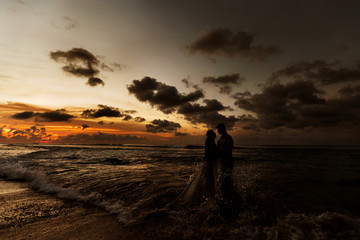 Silhouettes of the bride and groom hugging on the beach at sunset standing in the sea water