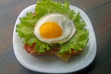 Preparing a sandwich with scrambled eggs, bacon and cheese