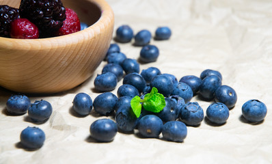 An isolated wooden bowl full of blueberries and wildberries with plain soft background decorated by fresh mint and with a few blueberries around on the paper