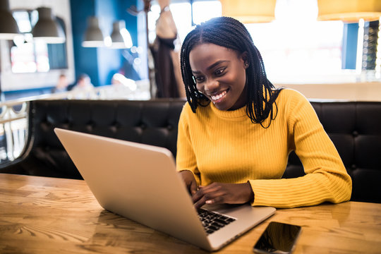 Human and technology. Young african woman typing on laptop, texting friends via social networks. Student girl browsing Internet, using free wi-fi, sitting at cafe
