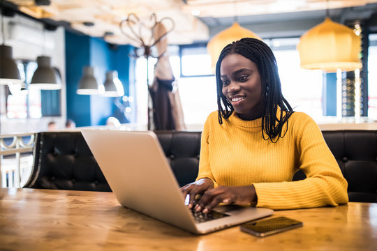 African american woman use laptop browse in internet in a cafe
