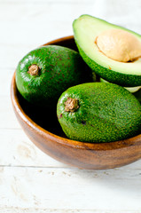 Avocado in a wooden bowl on a white wooden background